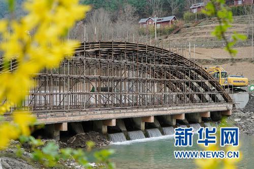 3月24日,位于甘肃省陇南市康县的国家4A级旅游景区花桥村内一座拱桥正在加紧施工。 新华社发(郎兵兵 摄)