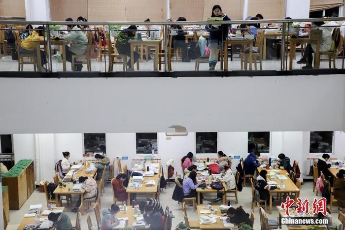 资料图:贵州民族大学逸夫图书馆内,考研学生正在看书复习。 中新社记者 瞿宏伦 摄