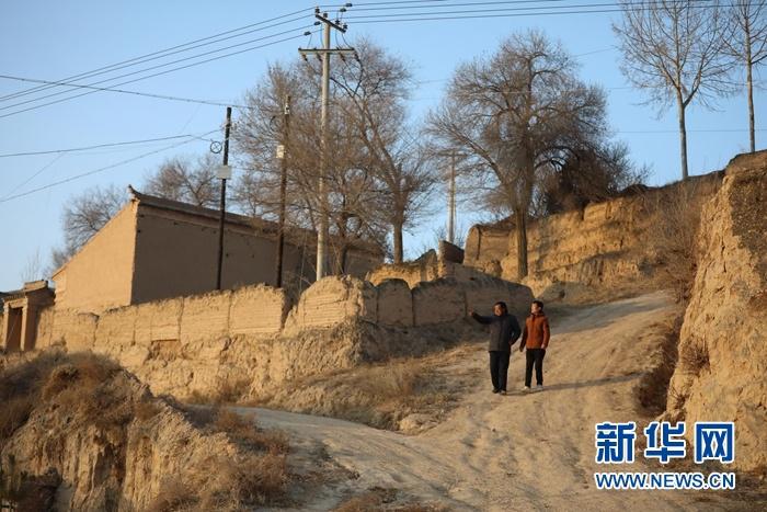 1月5日,在会宁县韩家集镇袁家坪村,任长太(左)和村干部在走访村民路上。新华社记者 马希平 摄