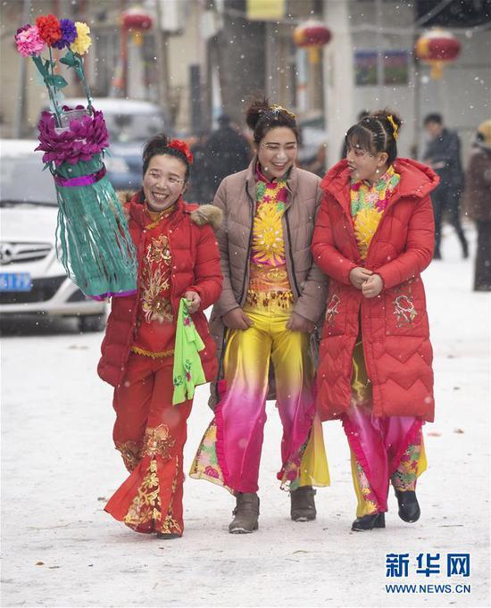2月17日,在甘肃省陇南市武都区鱼龙镇卯家庄村,高山戏演员在雪中走向戏台。 新华社记者 才扬 摄