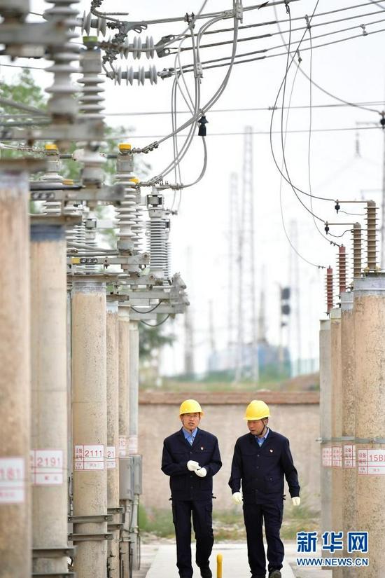 8月17日,石瑾(左)和同事在变电所内巡视。新华社记者 杜哲宇 摄