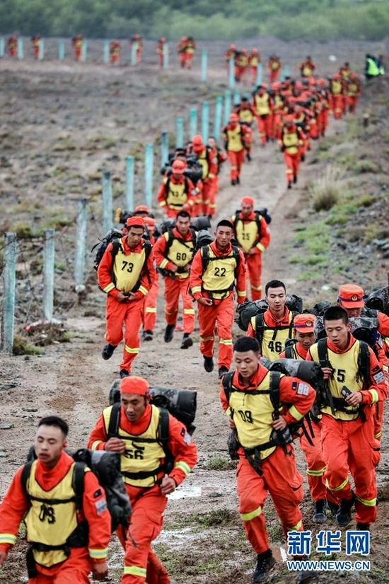 参赛队员正在进行山地5公里负重越野。 新华网发(龙智祥 摄)