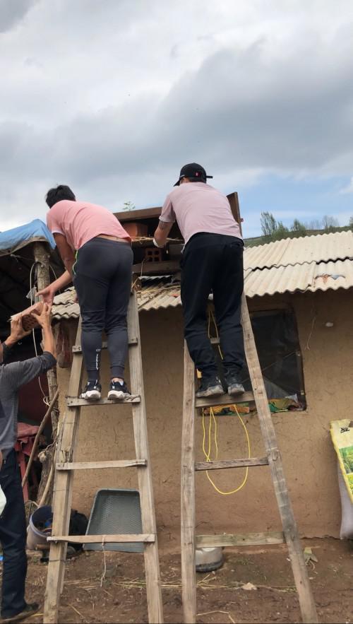 (图为阖木堂工作人员为贫困老人做屋顶防雨)
