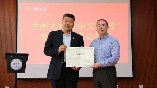 兰州大学副校长范宝军(左)向兰州大学文学院1992级校友代表颁发捐赠证书。(兰州大学文学院供图)