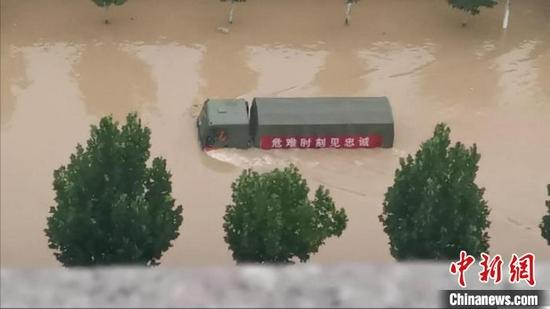 图为7月21日郑州东部地区被洪水围困,一辆军车在洪水中破浪前行。 张佳琪 摄