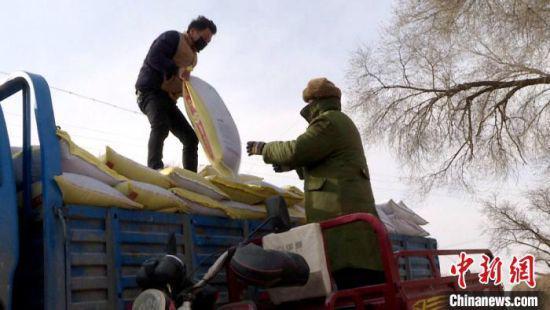2月上旬以来,甘肃乡村庄稼人陆续在田间地头迎来春耕春播。图为定西市安定区农户装卸农资物品。 郭强 摄