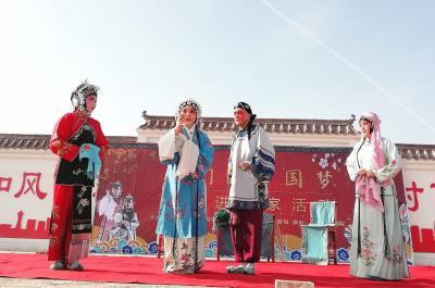 图为演员给村民们表演节目。