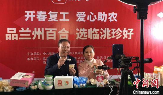 """月27日晚,甘肃定西市临洮县委书记石琳(左一)走进网络直播间,线上当起""""店小二""""推销农产品。图为石琳在直播间试吃即食百合。 张婧 摄"""