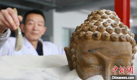 """在甘肃伯骊江3D打印科技有限公司内,56岁的""""玩""""沙人潘炳庆清理由沙子打印佛像模型。(资料图) 高展 摄"""
