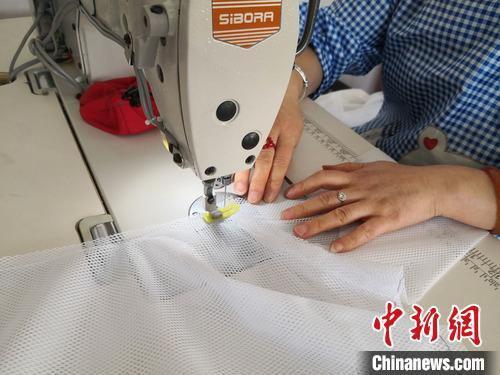 图为工人们缝制衣服。