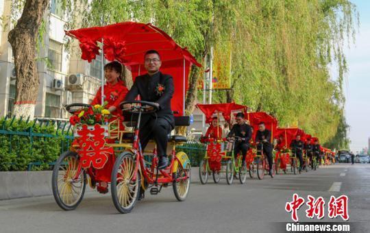 """5月4日,甘肃庆阳市举行主题为""""五四精神革故鼎新 移风易俗青年先行""""的集体婚礼,倡导移风易俗,抵制天价彩礼,树立文明节俭的新婚育观。 陈飞 摄"""