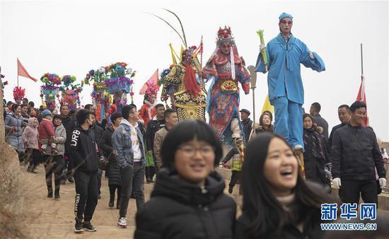 2月19日,在甘肃省陇南市武都区马街镇寺背村,社火队演员参加巡游表演。 新华社记者 才扬 摄