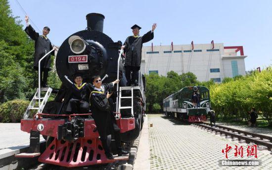 6月12日,兰州交通大学校园内的蒸汽机火车头吸引大学生拍摄怀旧毕业照。中新社记者 杨艳敏 摄