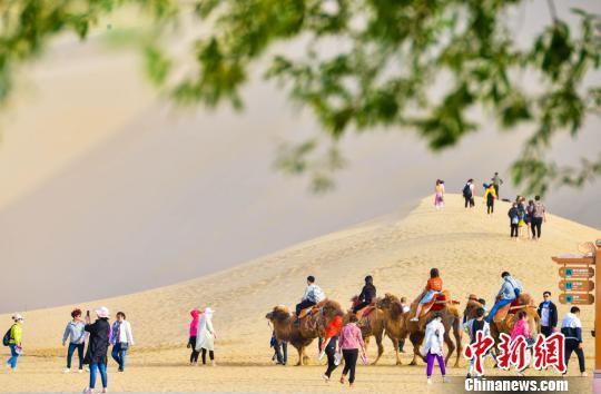 图为5月1日,中外游客在鸣沙山月牙泉景区观光游览。 王斌银/摄