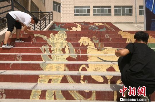 """近日,兰州城市学院20多名学生在老师指导下,为校园台阶、井盖""""换装"""",让原本单一的校园变得""""五彩缤纷""""。图为同学们正在台阶作画。 刘玉桃 摄"""