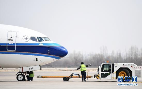 2月22日,机务人员在停机坪上为一架飞机做起飞前准备工作。新华社记者陈斌摄