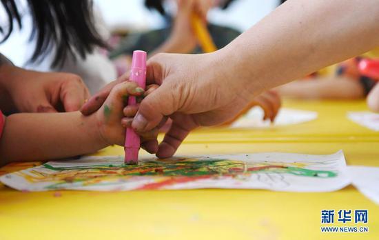 5月27日,中建三局西北公司的志愿者与孩子一起画画。新华社记者 陈斌 摄