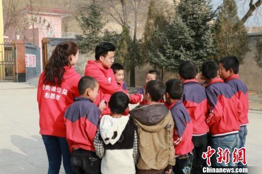图为志愿者们跟孩子们做游戏。(资料图) 钟欣 摄