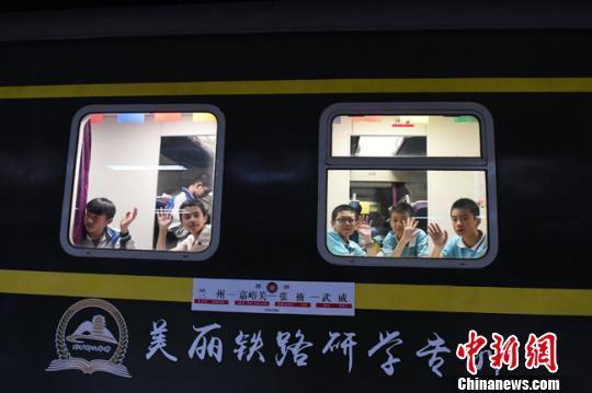 """6月12日晚,乘坐全国首列""""研学旅行专列""""的学生和送行的亲友们告别。 杨艳敏 摄"""
