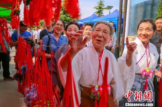 图为甘肃庆阳端午香包民俗文化节期间,日本友人参观游览。 陈飞 摄