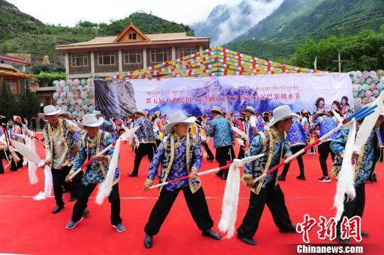 """男子们列成长队,吆喝呼应,摆出威武的""""龙阵舞"""",展示着山里人的粗犷与豪放。 李岩 摄"""
