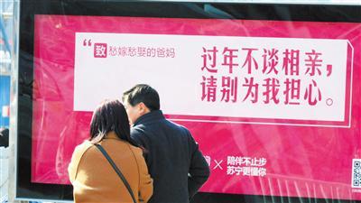 """2月13日,兰州市客运中心门前,乘客从一""""暖心""""广告文案前走过。首席记者 裴强/摄"""