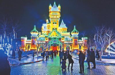 游客在灯光映衬下的方特城堡前拍照留念。