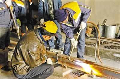施工人员干燥铁轨轨头。
