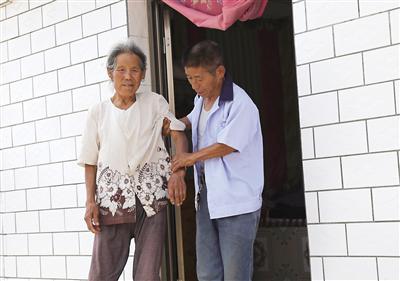 王雄(右)照顾毛靛兰老人 记者 金奉乾供图