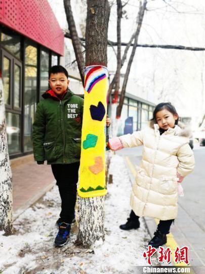"""连日来,在兰州创意文化产业园内正进行一场创意手工编织活动,一棵棵树木""""穿上""""了花花绿绿的个性毛衣。 钟欣 摄"""