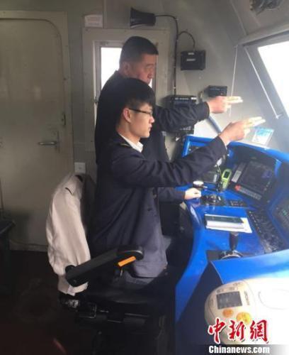 """近日,中国铁路总公司党组授予99名铁路职工""""铁路工匠""""的荣誉称号,兰州西机务段兰州客运车间电力机车司机郑云鹏获此殊荣。图为郑云鹏(后)正在指导帮助年轻火车司机提升技能。 丁思 摄"""