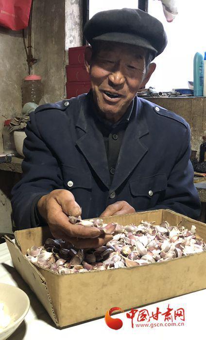 黄智华老人向记者展示收获的大蒜