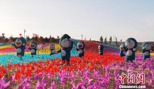 """连日来,300组不同主题的稻草人""""联盟""""现身于地处黄土高坡的甘肃兰州榆中县来紫堡乡,进行为期70天的文化艺术展览,旨在引领民众关注环保。图为用稻草制作的多啦A梦。 崔琳 摄"""