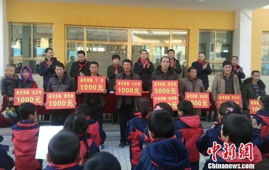 图为吊坪村部分学生家长代子女领奖助学金。 艾庆龙 摄