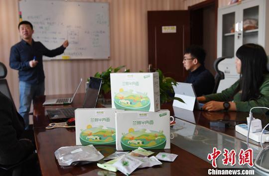 图为邓博士和他的团队正在商讨市场推广方案。 杨艳敏 摄