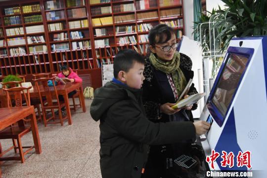 """兰州市西固区街头建成一家""""迷你""""图书馆,为市民提供阅读、借阅等服务。 杨艳敏 摄"""