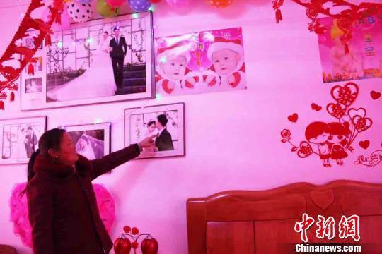 甘肃清水县后坡村村民李小燕特意穿了件喜庆的新衣服,为儿子史俊峰布置的新房就在小洋楼的二层,婚纱照悬挂在洁白的墙上。 徐雪 摄