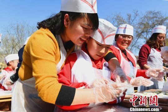 """小学生现场和家长、老师学习""""滚""""元宵,庆祝传统佳节,体验传统民俗的乐趣。 李浩 摄"""