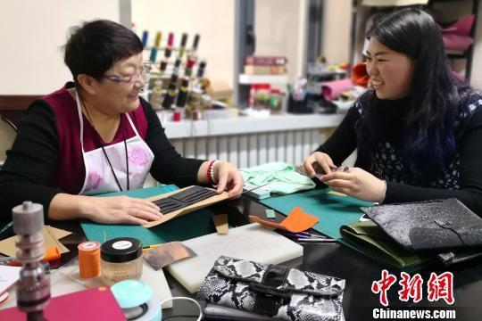 去年上半年,60岁的李丽和53岁的李霞姐妹俩在家人的提议下,开办手工皮具制作工作室,当起时尚创客,如今她们是生意越来越好。图为指导顾客做皮具。 刘玉桃 摄