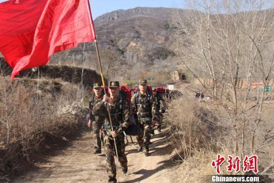 消防官兵背负30公斤重的背囊,徒步行走十余公里的山路。 段雅婷 摄