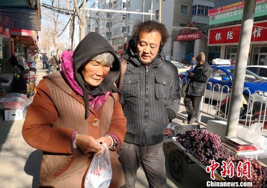 1月11日,张巨芳老人患上感冒,当地爱心人士陪老人买感冒药。 甘芬 摄