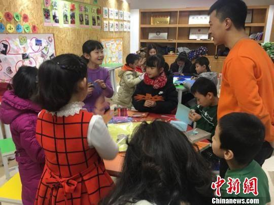 图为胡景蓉正在与老师交流自己制作面具的心得。 张婧