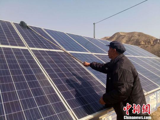 2月5日,兰州市皋兰县石洞镇豆家庄村村民王玉灿正在擦拭光太阳电池板。 闫姣 摄