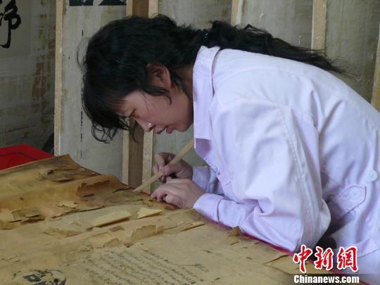 """黄静从事档案修复工作,如今已有13个年头了,经她""""医治""""而""""复活""""的档案已""""堆积如山""""。图为黄静在""""手术台""""上修复档案。 钟欣 摄"""
