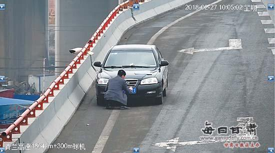 男子在东岗高速长下坡桥上停车安装车牌。监控截图