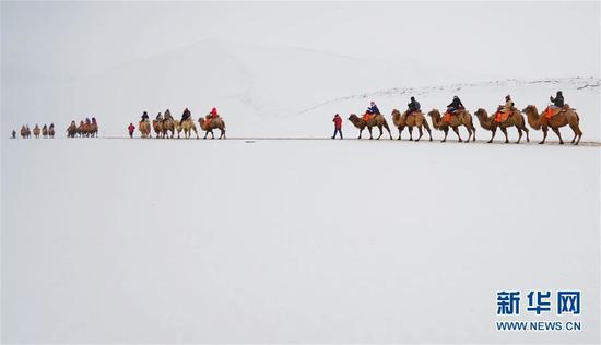 1月29日,游客在银装素裹的敦煌鸣沙山月牙泉景区游览。新华社发 马晓伟 摄