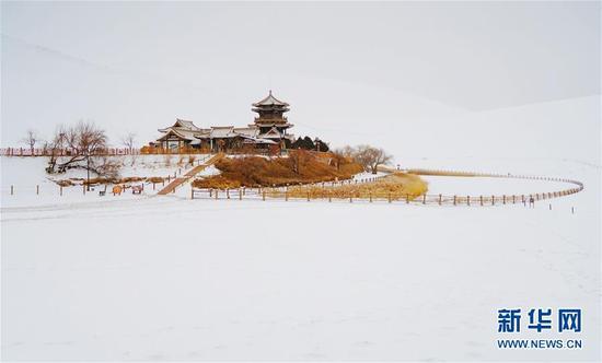 这是1月29日拍摄的银装素裹的敦煌鸣沙山月牙泉雪景。新华社发 马晓伟 摄