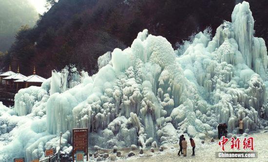 甘肃省积石山县大墩峡景区,冰挂美景吸引游人驻足留念。史有东摄