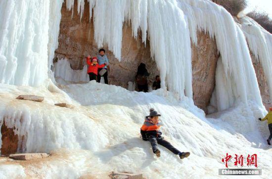 孩童在冰瀑前玩耍