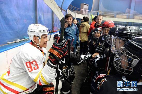 这是2017年4月20日,大陆冰球联赛(KHL)北京昆仑鸿星万科冰球龙队华裔球员袁俊杰(左)与冰球小学员们交流。新华社记者 王凯 摄